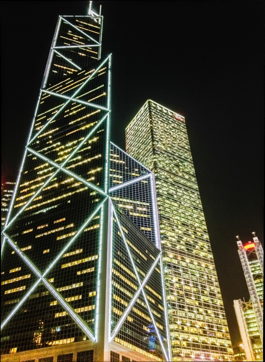 The Bank of China building stands proud in the middle of the financial district, making its stripes to reflect their blinking and colorful patterns off the neighboring buildings.