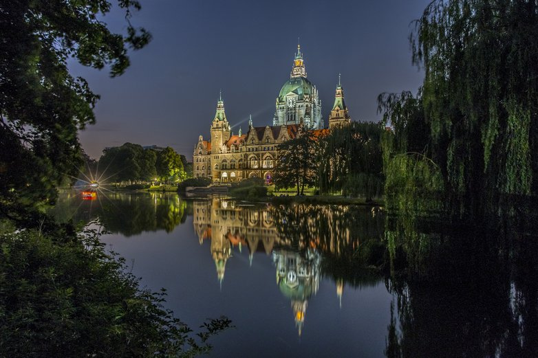 "The ""Neues Rathaus"" in Hannover at night before a peaceful reflecting pond."