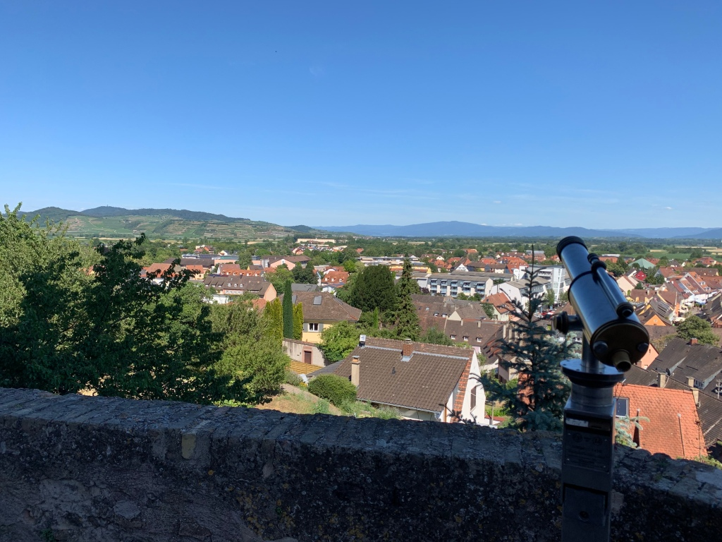 View from the top of Breisach looking eastward over the Kaiserstuhl towards the mountains of the Black Forest. In the foreground stands an eager for-pay telescope and an old wall.